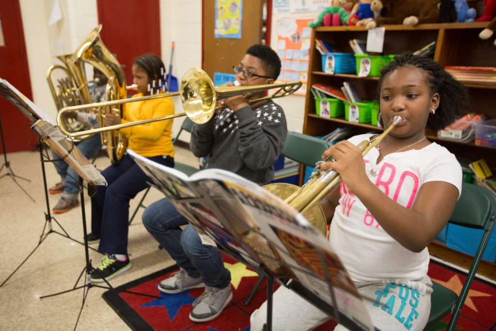 Four students playing brass instruments